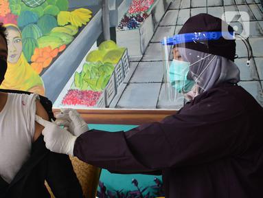 Seorang pedagang melakukan vaksinasi Covid-19  di Pasar Cisalak, Depok, Jawa Barat, Selasa (9/3/2021). Pemkot Depok melakukan vaksinasi Covid-19 kepada 213 pedagang di empat pasar tradisional yaitu Pasar Tugu, Pasar Sukatani, Pasar Agung, dan Pasar Cisalak. (merdeka.com/Arie Basuki)
