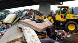 Petugas PPSU DKI Jakarta menggunakan alat berat saat membersihkan sampah sisa banjir di bawah Tol Becakayu, Cipinang Melayu, Jakarta Timur, Rabu (8/1/2020). Sampah sisa banjir tersebut selanjutnya diangkut ke TPA Bantar Gebang. (merdeka.com/Magang/Muhammad Fayyadh)