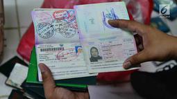 Satgas TPPO Bareskrim Polri menunjukkan paspor saat menggeledah kantor penampungan TKI ilegal di Bekasi, Jawa Barat, Jumat (23/3). Polisi menemukan barang bukti berupa paspor, KTP dan dokumen penting lainnya. (Liputan6.com/Pool/Bareskrim Polri)