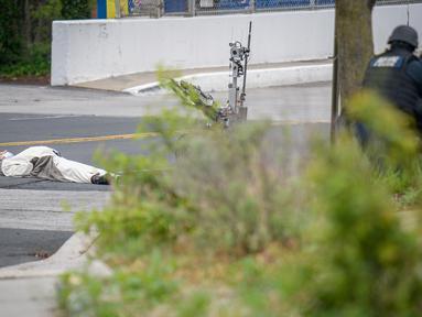 Seorang pria yang mengenakan kostum panda tergeletak di jalan usai ditembak oleh polisi di luar stasiun televisi Fox 45 di Baltimore, Amerika Serikat (AS), Kamis (28/4). Pria itu mengancam akan meledakkan stasiun televisi Fox 45. (REUTERS/Bryan Woolston)