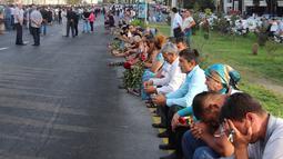 Warga duduk bersedih menunggu  iringan mobil jenazah Presiden Uzbekistan, Islam Karimov di Tashkent, Uzbekistan, (3/9).  Islam Karimov meninggal akibat penyakit stroke dan dugaan pendarahan di otak. (REUTERS/Muhammadsharif Mamatkulov)