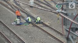 Petugas melakukan pengecekan wesel di perlintasan kereta api Cipinang-Jatinegara, Jakarta, Kamis (5/11/2020). Pengecekan perlintasan secara berkala di lakukan KAI untuk mengurangi potensi kecelakaan kereta api. (merdeka.com/Imam Buhori)