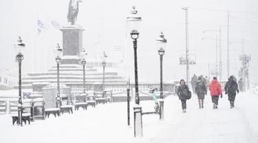 Orang-orang berjalan saat salju turun di Skeppsbron di Stockholm, Swedia (28/1/2021). Badan cuaca nasional Swedia, SMHI, telah mengeluarkan peringatan untuk salju lebat di Stockholm dan Uppsala. (Henrik Montgomery/TT via AP)