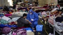 Petugas kesehatan Palang Merah memerika seorang pria yang mogok makan saat bersama yang lain menempati gereja Saint-Jean-Baptiste-au-Beguinage di Brussel, Senin (7/6/2021). Puluhan migran tanpa surat resmi telah memulai mogok makan sejak 23 Mei 2021. (AP Photo/Francisco Seco)