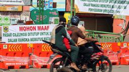 Warga melintasi pintu masuk kawasan Pasar Cileungsi yang dipenuhi spanduk penutupan, Kabupaten Bogor, Selasa (2/6/2020). Penutupan sementara kegiatan jual beli di Pasar Cileungsi terkait adanya tujuh pedagang yang positif terinfeksi virus COVID-19. (Liputan6.com/Helmi Fithriansyah)