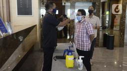 Petugas mengecek suhu tubuh pengunjung yang akan menginap di Hotel Grand Whiz Poins Simatupang, Jakarta, Kamis (16/4/2020). Di tengah pandemi virus corona COVID-19, hotel ini menyediakan paket isolasi mandiri selama 14 hari dengan harga Rp 6.500.000. (merdeka.com/Dwi Narwoko)