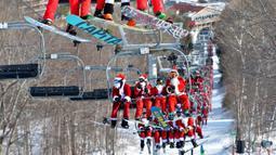 Para pemain ski berpakaian seperti Sinterklas menaiki lift ski selama berpartisipasi dalam acara tahunan Santa Sunday di Sunday River Resort yang terletak di Kota Newry, Amerika Serikat, Minggu (8/12/2019). Santa Sunday merupakan acara amal tahunan untuk River Fund Charity. (Joseph Prezioso / AFP)