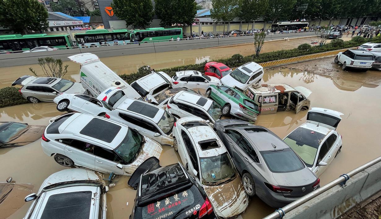 Mobil-mobil terendam banjir setelah hujan lebat melanda kota Zhengzhou di provinsi Henan tengah China (21/7/2021). Luapan sungai menggenangi jalan-jalan dan membuat kendaraan terbawa arus setelah curah hujan 200 mm turun dalam satu jam. (AFP/STR)