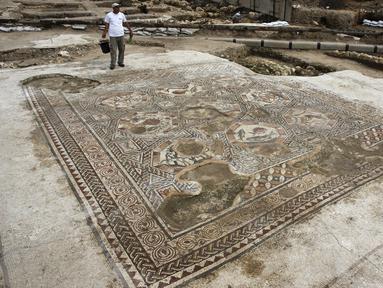 Seorang peneliti sejarah kuno saat ingin membersihkan lantai yang menampakkan gambar - gambar seperti  ikan dan binatang lainnya di Tel Aviv, Israel, Senin (16/11/2015). Tempat ini telah ada pada zaman Romawi dan periode Bizantium.  (REUTERS/Nir Elias)