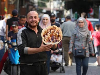 "Seorang pedagang Suriah memperlihatkan panekuk tradisional yang dikenal sebagai ""Naaem"" yang biasa disajikan selama Ramadhan, di Shaqhoor Damaskus pada 28 April 2021. Tahun demi tahun, makanan Ramadhan menjadi lebih hemat di Suriah yang dilanda perang dan ekonomi yang memburuk. (LOUAI BESHARA/AFP)"