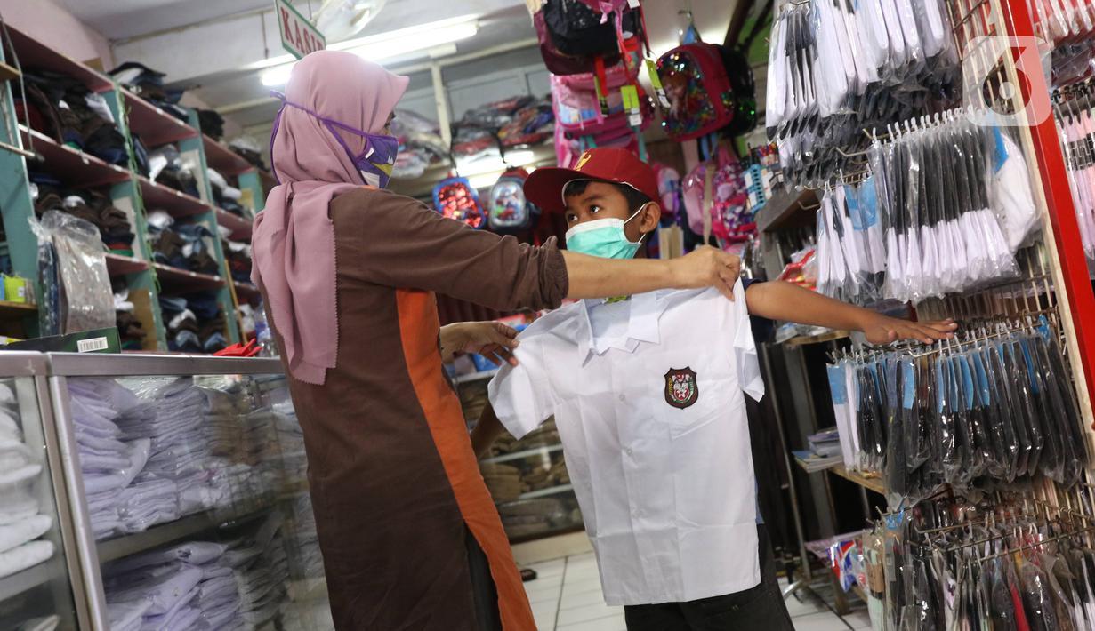 Pembeli mencoba seragam sekolah baru kepada anaknya di salah satu toko di Tangerang, Banten, Selasa (2/6/2020). Menjelang tahun ajaran baru, sejumlah pedagang di tempat tersebut mengeluh karena omzet penjualan seragam sekolah menurun drastis akibat pandemi COVID-19. (Liputan6.com/Angga Yuniar)