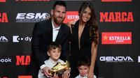 Pemain Barcelona, Lionel Messi didampingi istrinya Antonella Roccuzzo dan kedua putranya berpose setelah menerima trofi Sepatu Emas keenamnya selama acara penyerahan di Antiga Fabrica Estrella Damm, Barcelona, Spanyol (16/10/2019). (AFP Photo/Josep Lago)