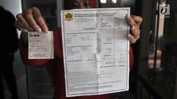 Penghuni memperlihatkan menunjukkan bukti pembayaran listrik bulanan di salah satu unit Apartemen Mediterania Palace, Jakarta, Rabu (31/7/2019). Pemadaman listrik diduga karena perseteruan pengelola apartemen baru dan pengelola lama yang belum selesai. (merdeka.com/Iqbal S. Nugroho)