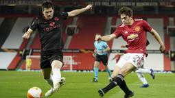 Gelandang Manchester United, Daniel James (kanan) melepaskan tendangan yang coba diblok gelandang Real Sociedad, Igor Zubeldia dalam laga leg kedua babak 32 Besar Liga Europa 2020/21 di Old Trafford Stadium, Kamis (25/2/2021). Manchester United bermain imbang 0-0 dengan Sociedad. (AP/Dave Thompson)