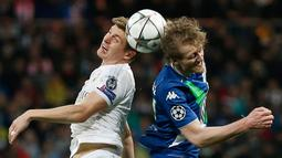 Gelandang Real Madrid, Toni Kroos (kiri) berebut bola dengan penyerang Wolfsburg, Andre Schurrle di leg kedua liga Champions di Santiago Bernabeu, Spanyol (13/4). Madrid menang atas Wolfsburg dengan skor 3-0. (Reuters/Sergio Perez)