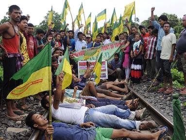 Ratusan pengunjuk rasa dari Front Rakyat Pribumi Tripura (IPFT) melakukan pemblokiran jalur rel kereta api saat menggelar demo di Khamtingbari di dekat perbatasan Agartala, India, Senin (10/7). (AFP Photo/ Arindam Dey)