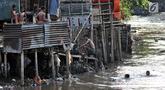 Anak-anak berenang di bawah jamban yang berada di bantaran Kali Ciliwung, Jakarta, Senin (19/11). Saat ini, tercatat sekitar 500 ribu penduduk DKI Jakarta tidak memiliki akses sanitasi yang layak. (Merdeka.com/Iqbal Nugroho)