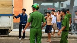 Pecandu narkoba yang berhasil ditangkap usai melarikan diri dari pusat rehabilitasi di Dong Nai, Vietnam, Senin (24/10). Lebih dari 500 pecandu narkoba kabur menjebol dinding dan merusak jendela menggunakan tongkat serta alat pemadam kebakaran. (STR/AFP)