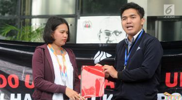 Presiden BEM KM Universitas Gadjah Mada (UGM) Obed Kresna Widyapratistha (kanan) menyerahkan kado buku merah kepada perwakilan Biro Humas KPK Brigita Simbolon pada aksi simpatik di Gedung KPK Jakarta, Senin (10/12). (Merdeka.com/Dwi Narwoko)