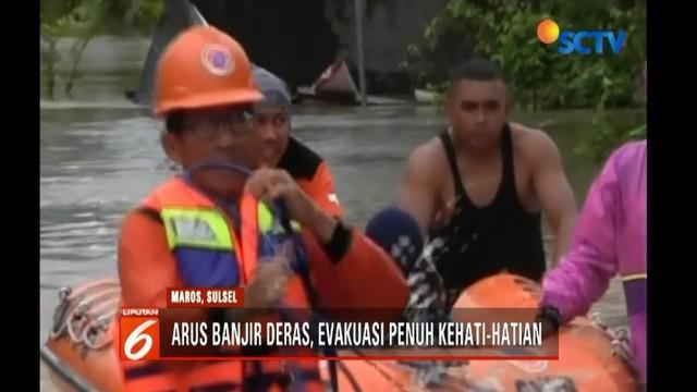 Seorang ibu dan anaknya terkurung banjir setinggi lebih dari satu meter di Moncongloe, Maros, Sulawesi Selatan. Beruntung, petugas berhasil mengevakuasi dengan menyeret melalui perahu karet.