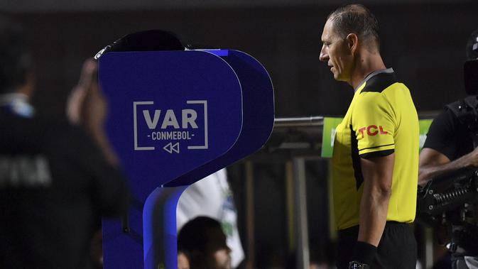 Wasit Nestor Pitana memeriksa VAR pada laga Copa America 2019 antara Brasil dan Bolivia. (AFP/Pedro Ugarte)