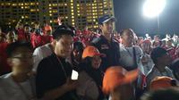 Sean Gelael menyapa fans setelah melakukan debut gemilang bersama Toro Rosso pada sesi latihan bebas F1 GP Singapura, Jumat (15/9/2017). (Bola.com/Muhammad Wirawan Kusuma)
