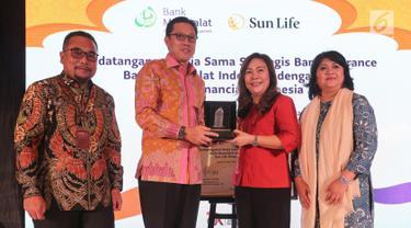 CEO Bank Muamalat Indonesia Achmad Kusna Permana dan Presdir Sun Life Financial Indonesia Elin Waty bertukar cindermata usai penandatanganan kerja sama Bancassurance, di Jakarta, Rabu (19/6). Kerjasama tersebut merupakan upaya meningkatkan layanan produk asuransi syariah. (Liputan6.com/HO/Astro)