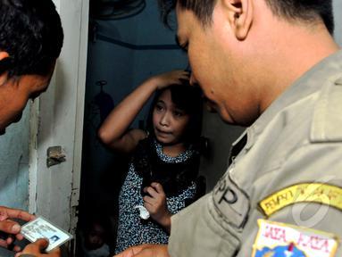 Petugas memeriksa KTP para penghuni kos di kawasan Sawah Besar Jakarta (28/4/2015) . Penertiban dilakukan untuk meminimalisir kegiatan prostitusi (Liputan6.com/Andrian M Tunay)