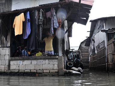 Warga beraktivitas saat banjir rob menggenangi permukiman Muara Angke, Jakarta, Selasa (22/1). Banjir air laut pasang atau Rob yang kembali melanda kawasan itu sejak 6 hari lalu membuat aktivitas warga sekitar terganggu. (Merdeka.com/Iqbal S. Nugroho)