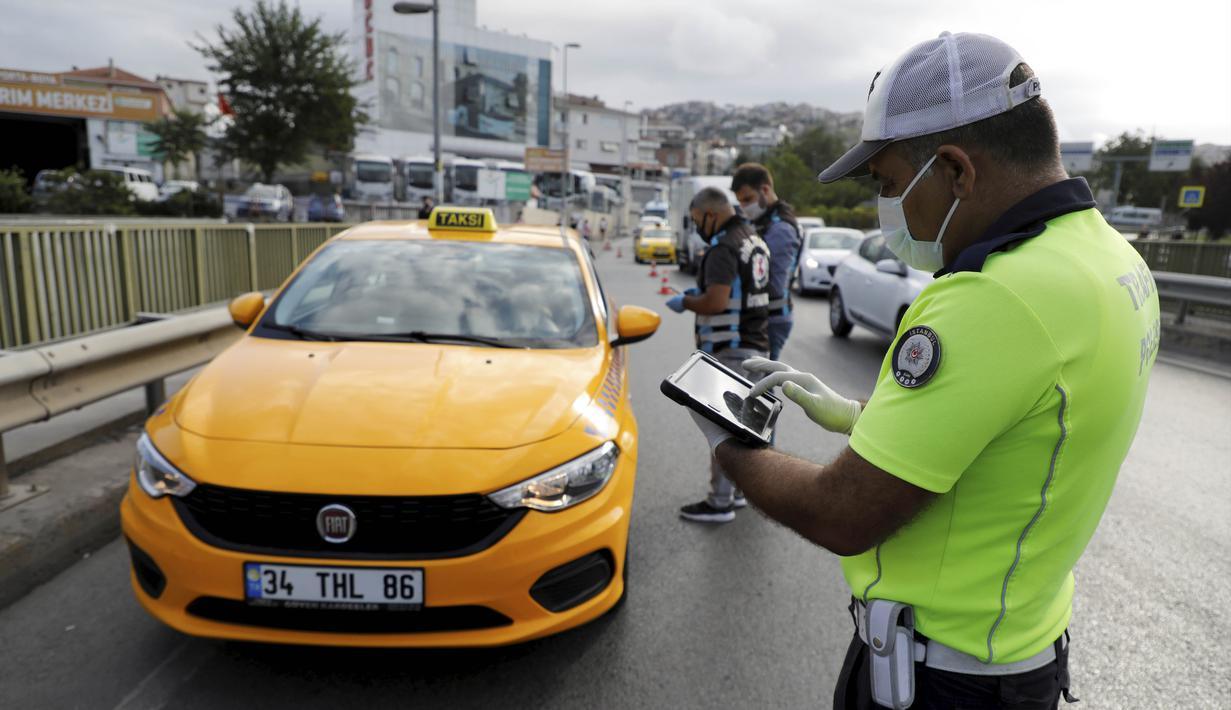 Polisi memeriksa taksi di pos pemeriksaan di Istanbul, Turki, Rabu (8/7/2020). Turki menggelar inspeksi nasional untuk mencegah penyebaran virus corona COVID-19. (Xinhua/Osman Orsal)