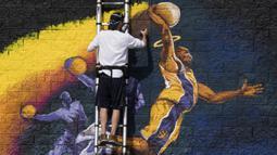 Seniman melukis mural peringatan untuk legenda NBA Kobe Bryant, yang tewas bersama putrinya Gianna dalam kecelakaan helikopter, di Hollywood Barat, California (30/1/2020). Kobe menghabiskan kariernya selama 20 tahun bersama  Los Angeles Lakers. (AFP/Mark Ralston)