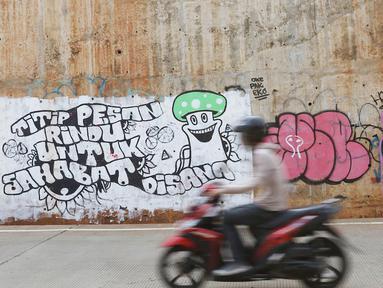 Pengendara sepeda motor melintas di sekitar dinding Jalan Tol Depok-Antasari (Desari), Ciganjur, Jakarta Selatan, Rabu (24/10). Aksi vandalisme menyebabkan dinding tol tampak kumuh dan tidak terawat. (Liputan6.com/Immanuel Antonius)