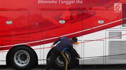 Petugas membersihkan bus transjakarta yang akan digunakan untuk pawai kemenangan tim sepak bola Persija Jakarta di kantor PT Transjakarta, Cawang, Kamis (13/12). Bus tersebut akan digunakan untuk pawai kemenangan Persija. (Liputan6.com/Immanuel Antonius)
