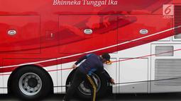 Petugas membersihkan bus transjakarta yang akan digunakan untuk pawai kemenangan tim sepak bola Persija Jakarta di kantor PT Transjakarta, Cawang, Kamis (13/12). Bus tersebut akan digunakan untuk pawai kemenangan Persija.(Www.sulawesita.com)