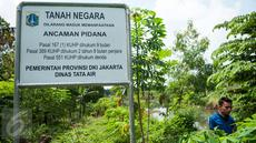 Sebuah plang tanah milik Pemprov DKI Dinas Tata Air terpasang di kawasan Waduk Giri Kencana, Cilangkap, Jakarta, Selasa (2/5). Pembangunan waduk itu terhenti karena masalah pembebasan lahan akibat sengketa kepemilikan tanah. (Liputan6.com/Gempur M Surya)