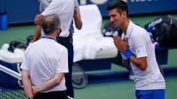 Petenis Serbia, Novak Djokovic berbicara dengan wasit setelah hantaman bolanya mengenai hakim garis saat kehilangan poin dari Pablo Carreno Busta (Spanyol) pada putaran keempat US Open 2020, di Flushing Meadows, (6/9/2020). Djokovic pun didiskualifikasi dari AS Terbuka 2020. (AP Photo/Seth Wenig)