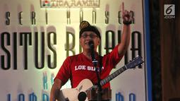Penyanyi Iwan Fals membawakan lagu sambil bermain gitar dalam Seri Konser Situs Budaya di Panggung Kita, Depok, Sabtu (3/3). Dalam konser tersebut, Iwan Fals membawakan lagu-lagu daerah seperti Tegining Amaq dan Sarompi Mpida. (Liputan6.com/Arya Manggala)