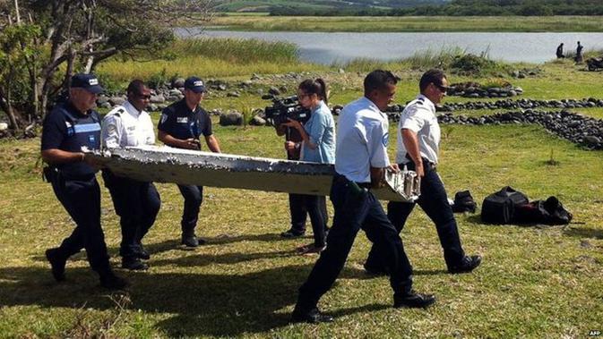 Polisi mengevakuasi benda diduga puing dari pesawat Malaysia Airlines MH370. (AFP/BBC)