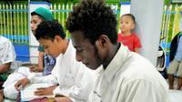 Mukhlis, Santri asal Papua tengah membaca Al Qur'an di sebuah Masjid Kota Kudus (Foto: Liputan6.com/Kusfitria Marstyasih)