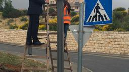 Wali Kota Yerusalem, Nir Barkat berpose dengan papan penunjuk jalan menuju Kedutaan Besar Amerika Serikat (AS) yang telah dipasang di Yerusalem, Senin (7/5). Papan itu bertuliskan bahasa Inggris, Ibrani, dan Arab. (Jerusalem Municipality via AP)