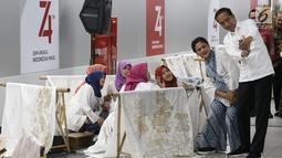 Presiden Joko Widodo dan Ibu Negara Iriana Jokowi  berselfie dengan sejumlah pembatik dalam acara batik kemerdekaan di Stasiun MRT Bundaran HI, Kamis (1/8/2019). Dalam kesempatan tersebut Jokowi berharap batik bisa dikembangkan sebagai sebuah brand. (Liputan6 com/Angga Yuniar)
