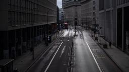 Seorang pria melintasi jalan kosong di Westminster, London, Inggris, Selasa, 12 Januari 2021. Inggris sedang menerapkan lockdown nasional ketiga untuk mengekang penyebaran virus corona COVID-19. (Victoria Jones/PA via AP)
