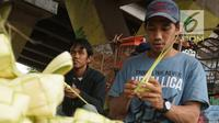 Pedagang menganyam kulit ketupat yang akan dijual di kawasan Bintaro, Jakarta, Sabtu (10/8/2019). Menjelang Idul Adha, para pedagang menjual kulit ketupat dengan harga sekitar Rp 8 ribu per sepuluh buah tergantung ukuran. (Liputan6.com/Herman Zakharia)