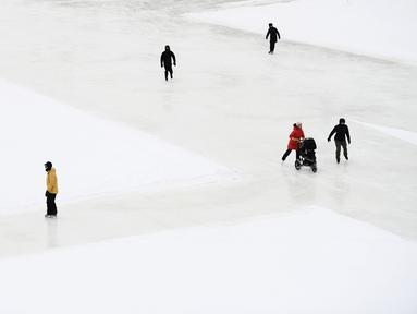 Orang-orang menyusuri Rideau Canal Skateway pada hari pembukaannya di tengah pandemi COVID-19 di Ottawa, Ontario, Kamis (28/1/2021). Kanal Rideau adalah Situs Warisan Dunia UNESCO. (Justin Tang/The Canadian Press via AP)