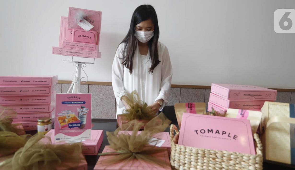 Pendiri Tomaple Gourmet Potato Donuts, Lala Ursula menyiapkan hampers untuk konsumen di salah satu outlet Tomaple di Jakarta, Sabtu (08/5/2021). Donat yang mampu berkreasi dengan pasar milenial dan didominasi warna pink mengusung tema #pinkboxhappines. (Liputan6.com/HO/Tomaple)