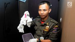Petugas Satpol PP membawa alat kontrasepsi saat razia panti pijat di BSD, Tangerang Selatan, Selasa (25/6/2019). Dalam razia tersebut ditemukan sepasang pria dan wanita tanpa busana dalam kamar. (merdeka.com/Arie Basuki)