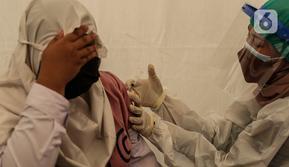 Petugas kesehatan menyutikkan vaksin covid-19 kepada seorang pelajar di Gudang Darurat Nasional Palang Merah Indonesia, Jakarta, Kamis (15/7/2021). PMI turut menggelar vaksinasi massal untuk mempercepat pencapaian target pemerintah untuk mewujudkan kekebalan komunitas. (Liputan6.com/Johan Tallo)