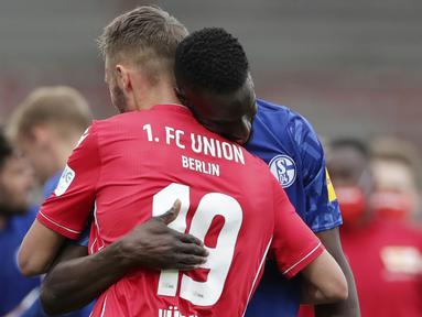 Pemain Union Berlin, Florian Huebner, berpelukan dengan pemain Schalke, Salif Sane, pada laga Bundesliga di Weserstadion Minggu (7/6/2020). Kedua tim bermain imbang 1-1. (AP/Michael Sohn)