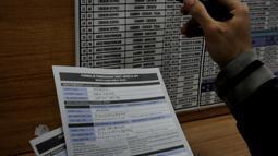 Seorang calon penumpang mengecek jadwal keberangkatan kereta api yang akan ditumpanginya, Jakarta, Jumat (13/3/2015). PT KAI akan menaikkan harga tiket per 1 April 2015, kenaikan dipengaruhi oleh fluktuasi harga BBM. (Liputan6.com/Johan Tallo)