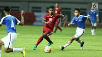 Penyerang Timnas Indonesia U-16, Amirudin Bagus Kahfi (tengah) mencoba melewati kawalan pemain Singapura U-16 saat laga persahabatan di Stadion Wibawa Mukti, Kab Bekasi, Kamis (8/6). Indonesia U-16 menang telak 4-0. (Liputan6.com/Helmi Fithriansyah)